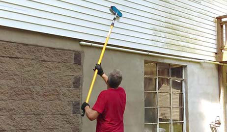 Mike uses a soft-bristled brush to clean the siding on a home.