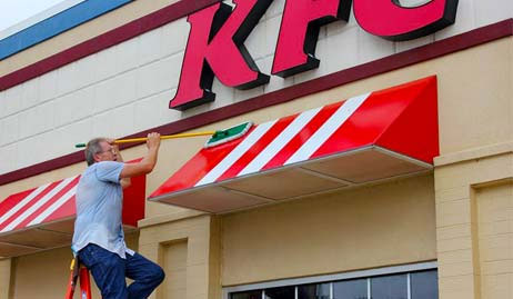 Mike uses a soft-bristled brush to clean an awning for KFC.
